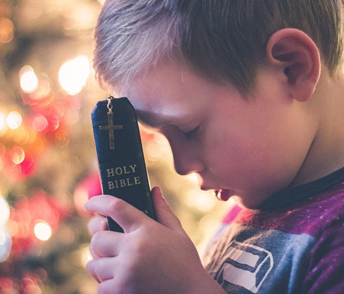 Child holding a bible and praying.